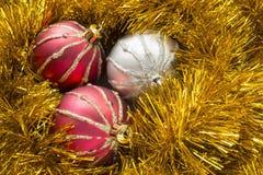 在闪亮金属片的三个圣诞节球 免版税库存图片