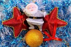 在闪亮金属片的圣诞老人和圣诞节装饰 库存照片