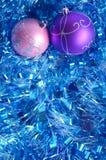 在闪亮金属片的桃红色和紫罗兰色圣诞节球 免版税库存图片