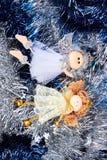在闪亮金属片背景的两个圣诞节天使 免版税库存照片
