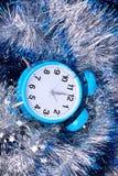 在闪亮金属片背景的蓝色闹钟 免版税图库摄影