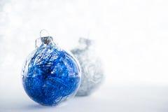 在闪烁假日背景的蓝色和白色xmas装饰品 库存图片