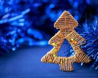 在闪烁蓝色背景的金黄圣诞树 Xmas和新年 库存图片