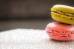 在闪烁银基地和黑暗的背景的桃红色和绿色蛋白杏仁饼干 免版税图库摄影