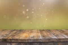 在闪烁绿色和金明亮的bokeh光前面的土气木桌 图库摄影