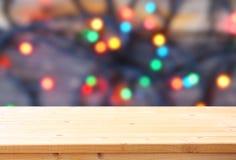 在闪烁colorfull明亮的bokeh前面的土气木桌点燃 免版税库存照片