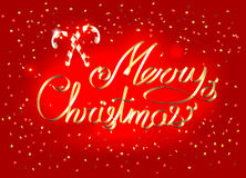 在闪耀的红色明亮的背景的圣诞快乐金黄丝带书法字法与甜棒棒糖 免版税库存照片