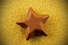 在闪耀的背景的巧克力星 免版税库存照片