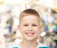 在闪耀的背景的微笑的小男孩 免版税图库摄影