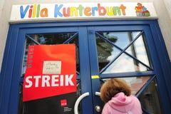 在闭合的幼儿园前面的女孩由于罢工 库存图片