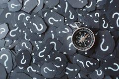 在问号背景的金属指南针 免版税库存照片