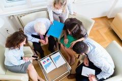 在队会议学习图表的五个商人 库存图片