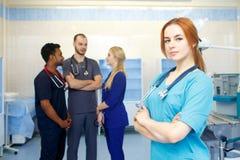 在队前面的女性医生,看与医疗队的照相机在背景中 年轻医生多种族队  免版税库存图片