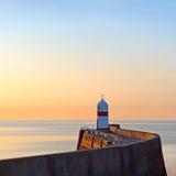 在防堤墙壁上的灯塔在日出期间 库存图片