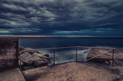 在防堤的日落与台阶 免版税库存图片