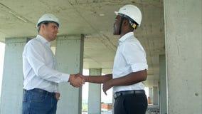 在防护盔甲和背心的英俊的建筑businessmans在建造场所握手 免版税库存图片