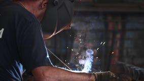 在防毒面具的焊工做电弧焊在慢动作的金属 影视素材