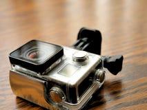 在防水住房盒的行动照相机在木书桌上 库存图片