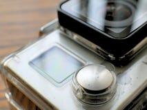 在防水照相机住房盒的行动凸轮在木书桌上 图库摄影