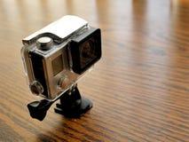 在防水照相机住房盒的行动凸轮在木书桌上 库存图片