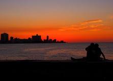 在防波堤上的年轻夫妇在日落在哈瓦那古巴 图库摄影