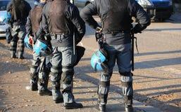在防暴装备的警察有在都市revo期间的防护盔甲的 库存图片