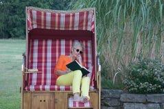 在阳光下一天,一张被顶房顶的柳条海滩睡椅的这名白肤金发的妇女只需要一本有趣的书 免版税库存图片