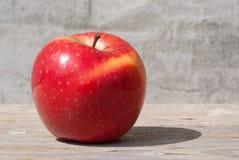 在阳光下的红色水多的坚实果子苹果在一个黑板对灰色墙壁 自然有机健康食物的概念 库存图片