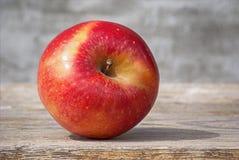 在阳光下的红色水多的坚实果子苹果在一个黑板对灰色墙壁 自然有机健康食物的概念 免版税库存照片