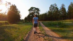 在阳光下走在乡下公路的女孩在日落 影视素材