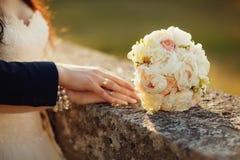 在阳光下年轻婚礼夫妇,陈列他们的圆环 定调子 图库摄影