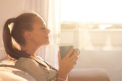 在阳光的女孩嗅到的咖啡 免版税库存图片