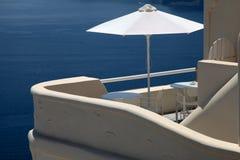 在阳台手段房子和爱琴海,圣托里尼的白色伞 库存照片