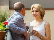 在阳台的夫妇饮用的咖啡 免版税库存图片