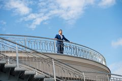 在阳台的确信的商人立场多云蓝天的 室外的礼服的人 查找的远期 认为 免版税库存照片