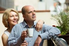 在阳台的年迈的夫妇饮料茶 库存照片