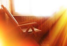 在阳台的Arnchair有剧烈的太阳的发出光线背景 免版税库存照片