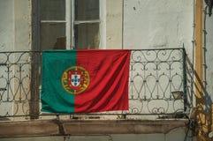 在阳台顶部铁扶手栏杆的葡萄牙旗子  免版税库存照片