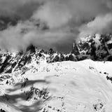 在阴霾的黑白多雪的岩石在冬天 免版税库存照片