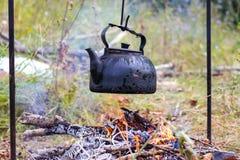 在阵营火的老水壶 免版税库存照片