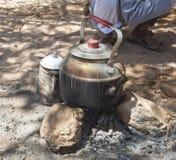 在阵营火的水壶在沙漠 库存图片