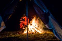 在阵营火附近的女孩与毯子 图库摄影