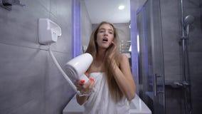 在阵雨的乐趣,毛巾的美丽的性感的年轻女人在她的手和调情的人上唱歌与一hairdryer在前面 股票视频