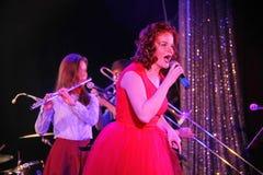 在阶段、音乐家流行音乐石小组薄荷和歌手安娜Malysheva 红色朝向的爵士乐岩石女孩唱歌 免版税库存照片