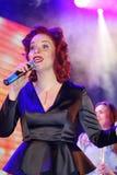 在阶段、音乐家流行音乐石小组薄荷和歌手安娜Malysheva 红色朝向的爵士乐岩石女孩唱歌 库存照片
