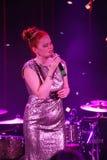 在阶段、音乐家流行音乐石小组薄荷和歌手安娜Malysheva 红色朝向的迷人岩石女孩唱歌 免版税库存图片