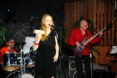 在阶段、音乐家流行音乐石小组薄荷和歌手安娜Malysheva 红色 红色朝向的迷人岩石女孩唱歌 库存图片