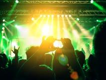 在阶段光前面的音乐会人群 免版税库存照片