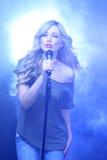 在阶段唱歌的美丽的白肤金发的摇滚明星 图库摄影