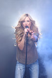 在阶段唱歌的美丽的白肤金发的摇滚明星 库存图片